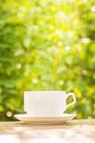 La tazza di caffè sulla tavola di legno con le foglie verdi ha offuscato il backgrou Immagini Stock