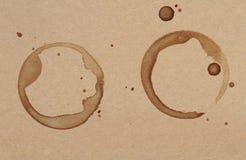 La tazza di caffè suona le macchie su una struttura della carta marrone Fotografia Stock Libera da Diritti