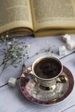 La tazza di caffè turco con i lukum e di cuore ha modellato il cioccolato accanto al vecchio libro Immagine Stock