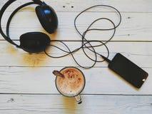 la tazza di caffè, uno smartphone e le cuffie mettono su un fondo bianco Immagini Stock