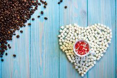 La tazza di caffè in pieno del piano delle caramelle mette sul fondo di legno blu-chiaro rustico Figura del cuore fatta dalle car Immagine Stock
