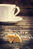 La tazza di coffe e lo zucchero di canna marrone con forma di cuore su vecchio corteggiano Fotografia Stock Libera da Diritti