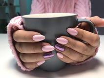 La tazza di tè calda di sera ha abbracciato a mano con il manicure sveglio interessante Fotografia Stock