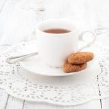 La tazza di tè con i biscotti sopra è servito sulla tavola di legno Fotografia Stock Libera da Diritti