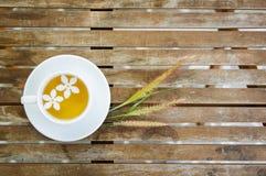La tazza di tè & del gruppo di erba di setaceus del Cenchrus fiorisce su di legno Fotografia Stock
