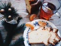 la tazza di tè, il dolce casalingo e l'Natale-albero si ramificano sulla tavola Immagine Stock
