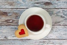 La tazza di tè nero e di cuore ha modellato i biscotti Fotografie Stock