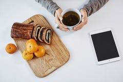 La tazza di tè rende il sembrare di mattina più luminoso Vaso moderno della tenuta della donna, mangiante mandarino e dolce rotol fotografia stock