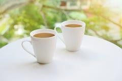 La tazza, due foggia a coppa, di tè o di caffè sulla tavola sul fondo luminoso del giardino Fotografia Stock