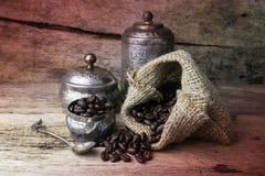 La tazza ed i chicchi di caffè d'argento in tela di sacco insaccano su backgroun di legno Fotografia Stock