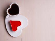La tazza ed il dolce di caffè a forma di cuore su legno sorgono Fotografia Stock Libera da Diritti