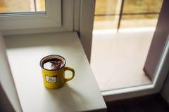 La tazza gialla di caffè è sul davanzale della finestra L'iscrizione sul cerchio Avete saputo? immagini stock