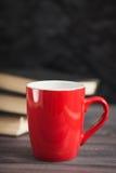 La tazza rossa ed i libri neri su un fondo scuro Fotografia Stock Libera da Diritti