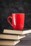 La tazza rossa ed i libri neri su un fondo scuro Immagine Stock Libera da Diritti