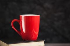 La tazza rossa ed i libri neri su un fondo scuro Immagine Stock
