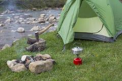 La tazza sta su un ceppo vicino al fuoco ad un campeggio fotografie stock libere da diritti