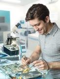 La technologie ou l'ingénieur répare le matériel électronique dans le facili de recherches Images stock
