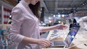 La tecnología moderna, cliente de la mujer selecciona y con el ordenador portátil en tienda de la electrónica metrajes
