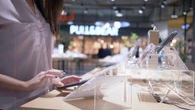 La tecnología moderna, cliente utiliza la tableta con la pantalla táctil en la sala de exposición del artilugio en la tienda de l metrajes