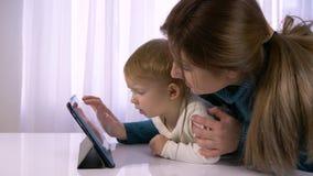 La tecnología moderna en relaciones de familia, niño feliz con la mamá se juega con la tableta en sitio brillante almacen de metraje de vídeo