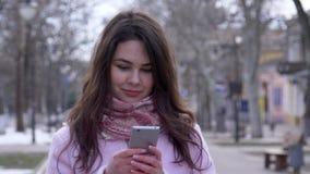 La tecnología moderna, hembra joven con el teléfono móvil comunica en Internet con los amigos durante paseo almacen de video