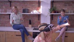 La tecnología VR, hembra joven en casco de la realidad virtual juega al juego moderno con la familia en cocina metrajes