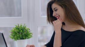 La tecnologia moderna, ragazza sorridente sta scrivendo in Internet con gli amici che per mezzo del computer che si siede alla ta