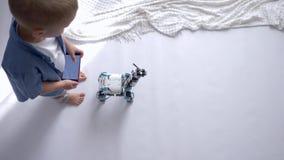 La tecnologia robot astuta, piccolo ragazzo del bambino è giocata dai giocattoli moderni su telecomando facendo uso dello smartph video d archivio