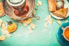 La teiera e la tazza di tè con i dolci e le rose fiorisce i petali sul fondo elegante misero del turchese Immagine Stock Libera da Diritti