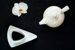 La teiera e la tazza ceramica bianca d'annata con tè su fondo scuro con l'orchidea fioriscono, spazio della copia, primo piano Fotografia Stock