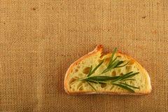 La tela con i rosmarini va sulla fetta di pane integrale Fotografia Stock Libera da Diritti