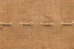 La tela da imballaggio con una allinea degli anelli di oro e della corda Immagini Stock