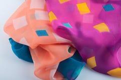 La tela multicolora suave de la gasa pone en el fondo blanco Fotografía de archivo