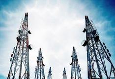 La telecomunicación se eleva con las antenas de TV y la antena parabólica en el cielo azul claro Imagen de archivo