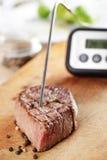 La température de contrôle à l'intérieur du bifteck Image libre de droits