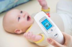 La température de mesure à un bébé Images libres de droits