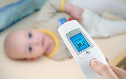 La température de mesure à un bébé Photos stock