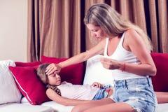 La température de mesure de mère de son enfant malade Enfant malade avec le hig image stock