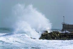 La tempesta del mare ondeggia lo schianto e la spruzzatura contro il molo Fotografie Stock Libere da Diritti