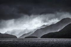 La tempesta drammatica si rannuvola gli strati retrocedere delle montagne sopra il suono dubbioso in Nuova Zelanda nel monocromio Immagini Stock