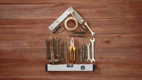 La temps-faute de vue supérieure d'une main s'étendant dessus wodden la maison conceptuelle de table utilisant les outils et la s