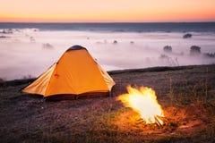 La tenda arancio sulla mattina nebbiosa sulla collina di cui sopra rive fotografie stock