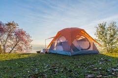 La tenda di campeggio in campeggio sopra la montagna con l'alba a fa Immagine Stock