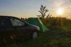 La tenda di campeggio e un'automobile nella mattina soleggiata all'estate del fondo abbelliscono Concetto di ricreazione immagine stock