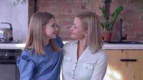La tendresse maternelle, portrait de mère de sourire avec la belle fille d'enfant s'embrassent et regardent le plan rapproché de