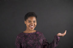 La tenencia africana de la mujer distribuye en fondo de la pizarra Fotografía de archivo libre de regalías