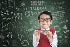 La tenencia alegre del estudiante del muchacho APRENDE el bloque Foto de archivo libre de regalías