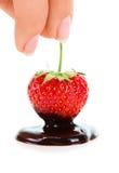 La tenencia de la mano de la mujer chocolate-sumergió la fresa Fotos de archivo libres de regalías