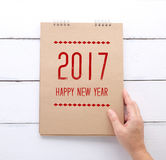 La tenencia de la mano recicla el cuaderno de papel con la Feliz Año Nuevo 2017 encendido Foto de archivo libre de regalías