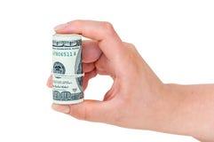 La tenencia de la mano rodó 100 dólares de billetes de banco Fotos de archivo